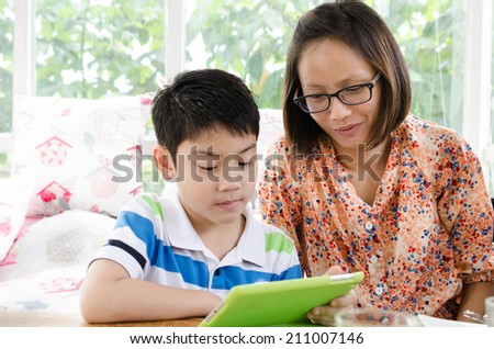 Portrait of little asian mother and son with tablet computer . - stock photo