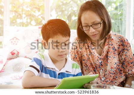 Portrait of little asian mother and son with tablet computer , with sun light .