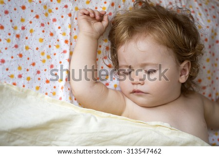 Portrait of little attractive lovely sweet with blonde soft curly hair cute male baby boy sleeping indoor in bed on colorful linen with floral pattern, horizontal picture - stock photo