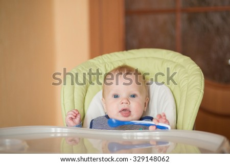 Portrait of little baby boy eating his first solid food