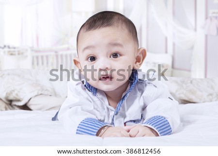 Portrait of little baby boy lying in the bedroom alone, looking on the camera - stock photo