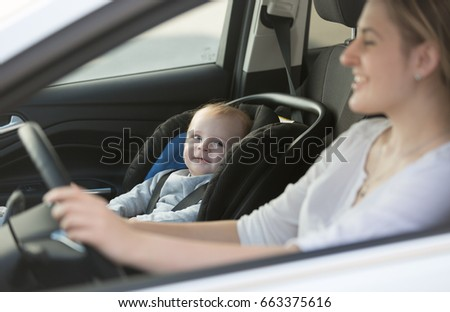 Portrait of little baby boy sitting in car at safety seat