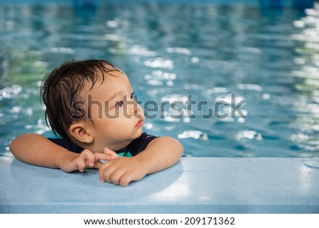 Portrait of little baby boy swimming in the swimming pool - stock photo