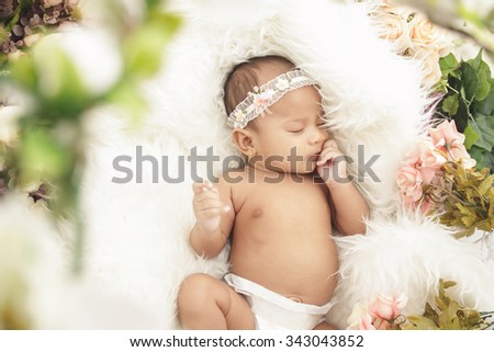 portrait of little baby girl sleeping comfy on fur blanket with flowers around - stock photo