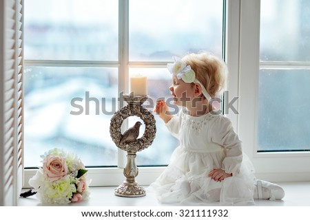 Portrait of little baby girls blonde in white dress sitting on a window and blowing out a candle - stock photo