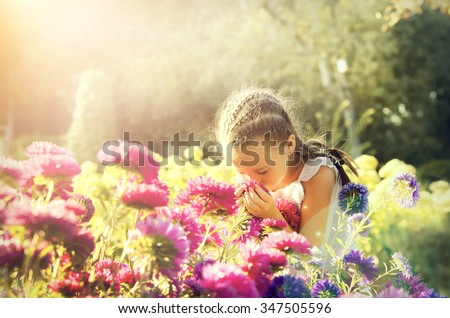 Portrait of little beautiful girl is smelling flowers - stock photo