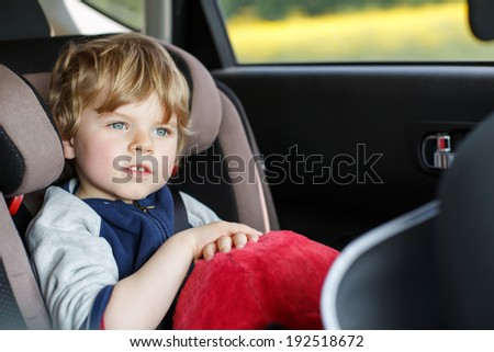 Portrait of little blond boy sitting in safety car seat - stock photo