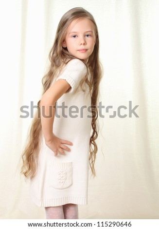 Portrait of little blond girl with hands on hips - stock photo