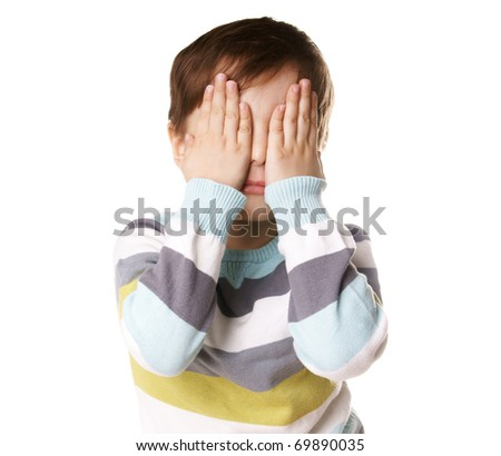 Portrait of little boy closed eyes with his hands isolated on white background - stock photo