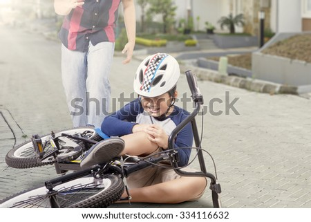 Portrait of little boy crying while holding his knee after falling from the bike with father coming for help - stock photo