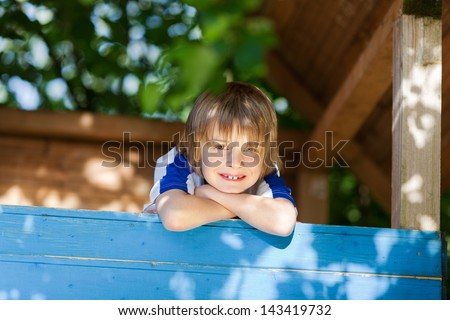 Portrait of little boy leaning on treehouse's wall at playground - stock photo