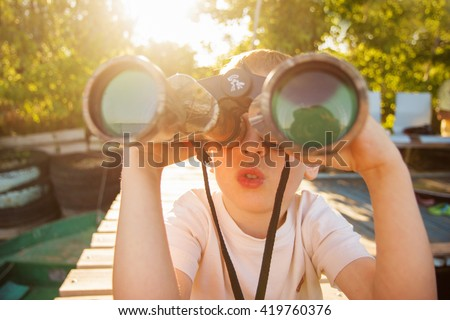 Portrait of little boy looking through binoculars on river bank. Cute kid with binoculars sitting on the pier on river. Focus on child. - stock photo