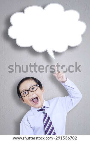 Portrait of little boy looks happy and pointing at empty cloud speech.