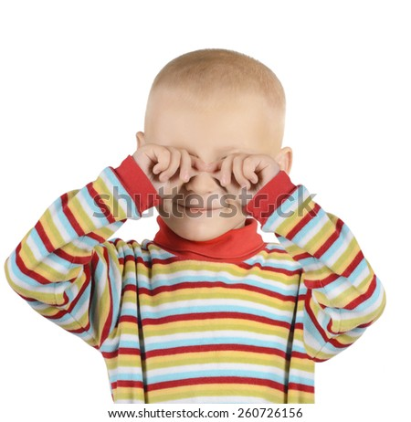 Portrait of little boy rubbing eyes with his hands isolated on white background - stock photo