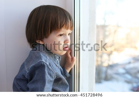 Portrait of little boy sits on sill and looks out of window in winter - stock photo
