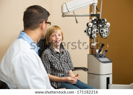 Portrait of little boy smiling while sitting with optometrist in store - stock photo