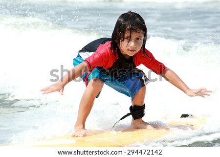 portrait of little boy surfing at ocean - stock photo