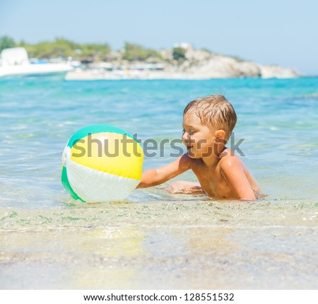 Portrait of little boy swimming and plaing with ball in the transparent sea - stock photo