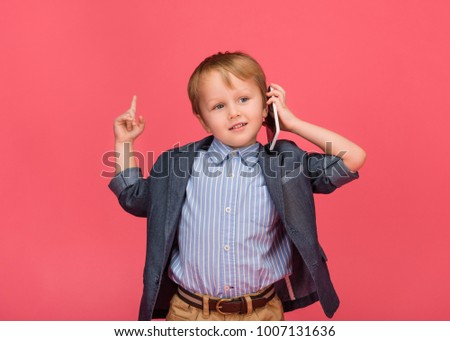 portrait of little boy talking on smartphone isolated on pink