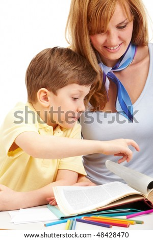 Portrait of little boy turning page of book with mother near by - stock photo
