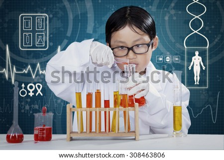 Portrait of little boy wearing coat and make experiments in the laboratory with chemical fluid - stock photo
