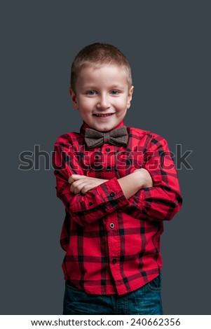 Portrait of little boy with emotion isolated on dark background