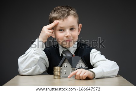 Portrait of little boy with home model and pile of coins on grey background. Concept of realty and investment - stock photo