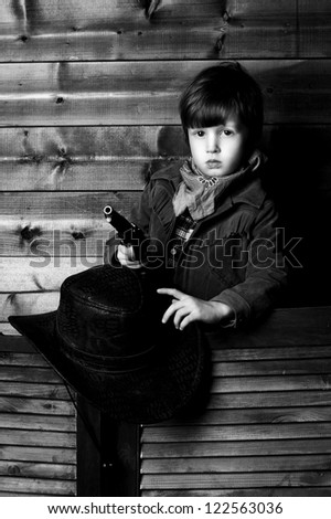 portrait of little calm cowboy holding his hat in one hand and gun in other - stock photo