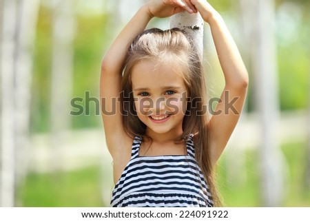 Portrait of Little caucasian girl, against green of summer park. - stock photo