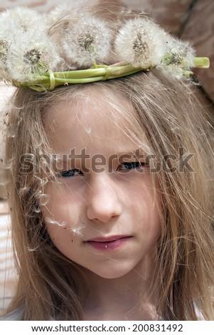 portrait of little caucasian girl in white dandelion garland - stock photo