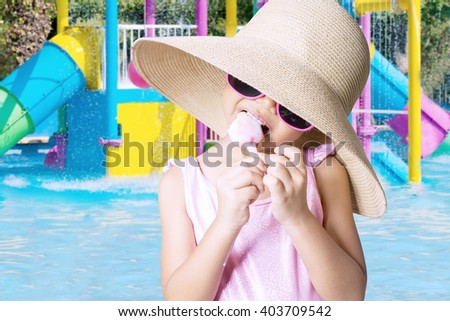 Portrait of little child standing on the pool while wearing swimsuit and hat, eating ice cream - stock photo