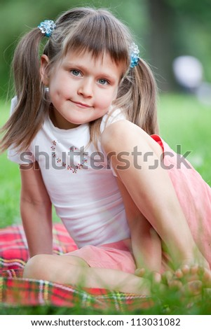 Portrait of little cute blond girl preschooler with ponytails sitting on the red plaid on green grass in summer - stock photo