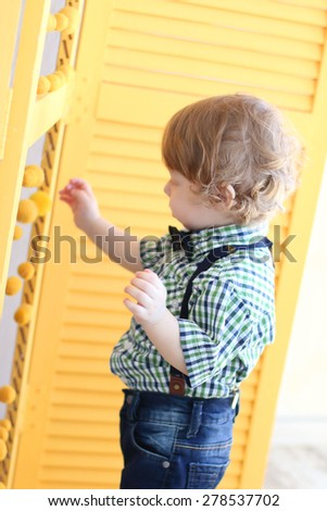 Portrait of little cute boy with curly hair touching screen with yellow balls - stock photo