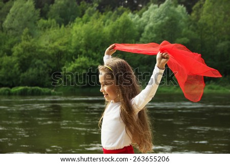 Portrait of little cute girl dance with red Scarf by the river - stock photo
