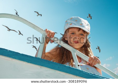 Portrait of little cute girl enjoying playing on boat on a hot sunny day. Seagulls in the sky. - stock photo