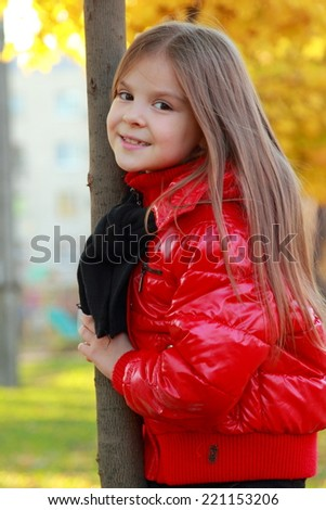 Portrait of little cute girl in a wreath from autumn yellow leaves/Nice little girl outdoor at autumn time - stock photo