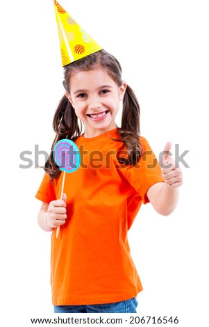 Portrait of little cute girl in orange t-shirt and party hat with colored candy showing thumbs up gesture - isolated on white. - stock photo