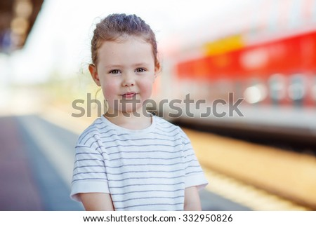 Portrait of little cute girl on railway station with train on background. Kid waiting for train and happy about a journey. People, travel, lifestyle concept - stock photo