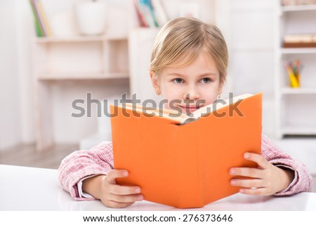 Portrait of little cute girl wearing pink suit. Girl sitting at table, smiling and reading book. Room interior as a background - stock photo