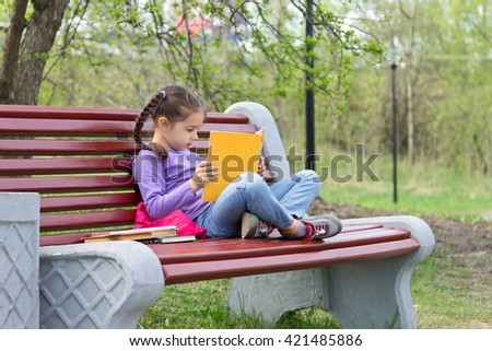 Portrait of little cute girl with open book sitting on the wooden bench in spring park - stock photo