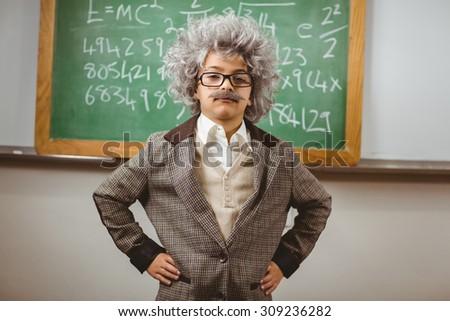 Portrait of little Einstein posing in front of chalkboard in a classroom - stock photo
