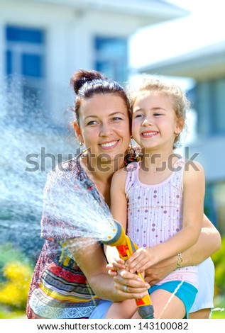 Portrait of little gardener girl with mother watering flowers on the lawn near cottage. Vertical view - stock photo