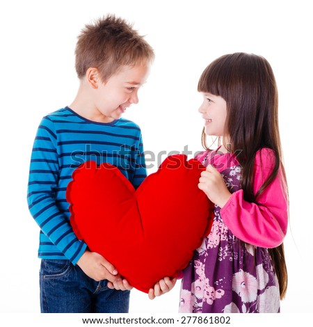 Portrait of little girl and boy holding a big red heart shaped pillow - stock photo