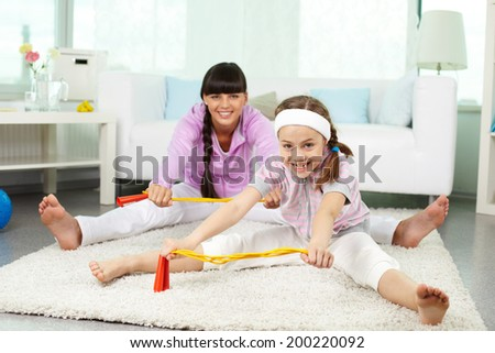 Portrait of little girl and her mother doing physical exercise for stretching at home - stock photo