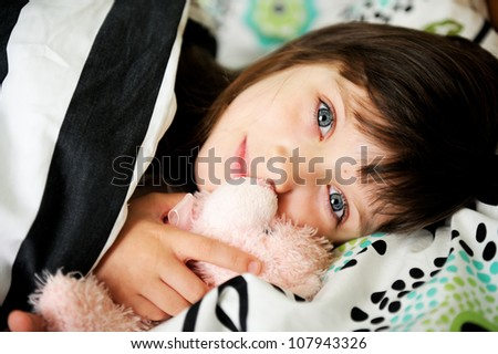 Portrait of little girl awaken in bed in early morning - stock photo