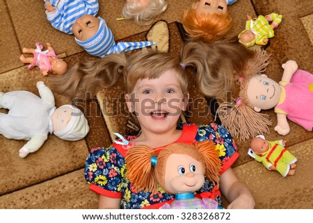 portrait of little girl(child, kid) with dolls on the carpet - stock photo