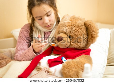 Portrait of little girl giving medicines to teddy bear - stock photo