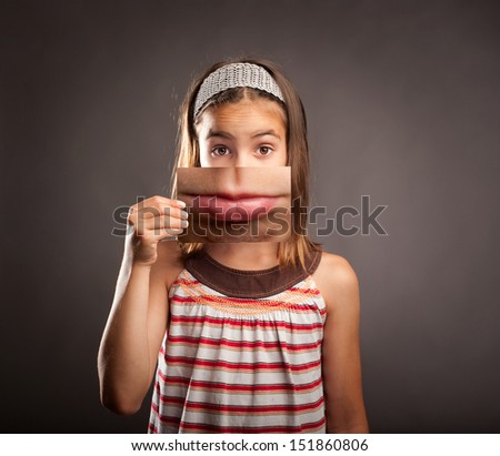portrait of little girl holding a photography of herself with sad expression - stock photo