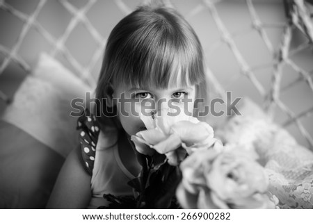 Portrait of little girl holding peonies - stock photo