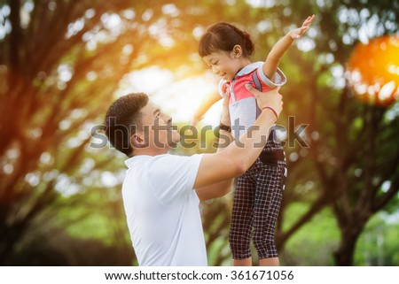 Portrait of little girl hugging her daddy with nature and sunlight, family concept - stock photo